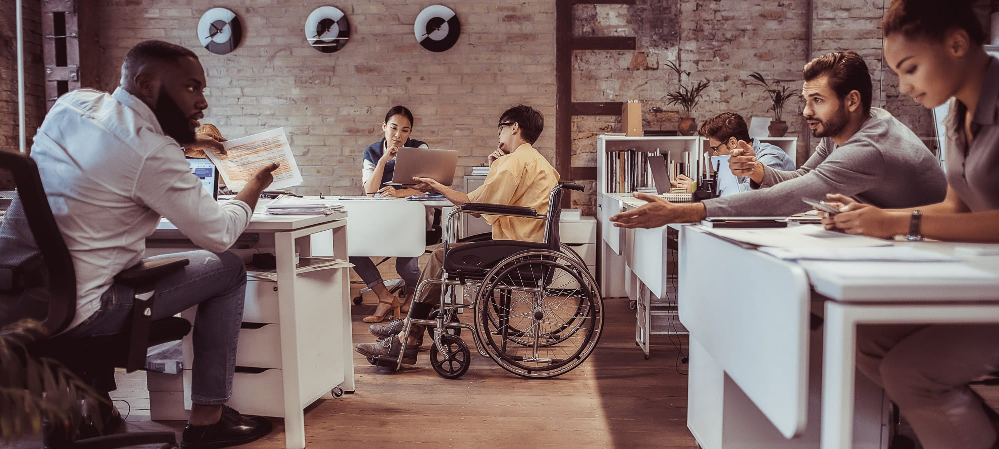 Wheelchair user with colleagues in the office