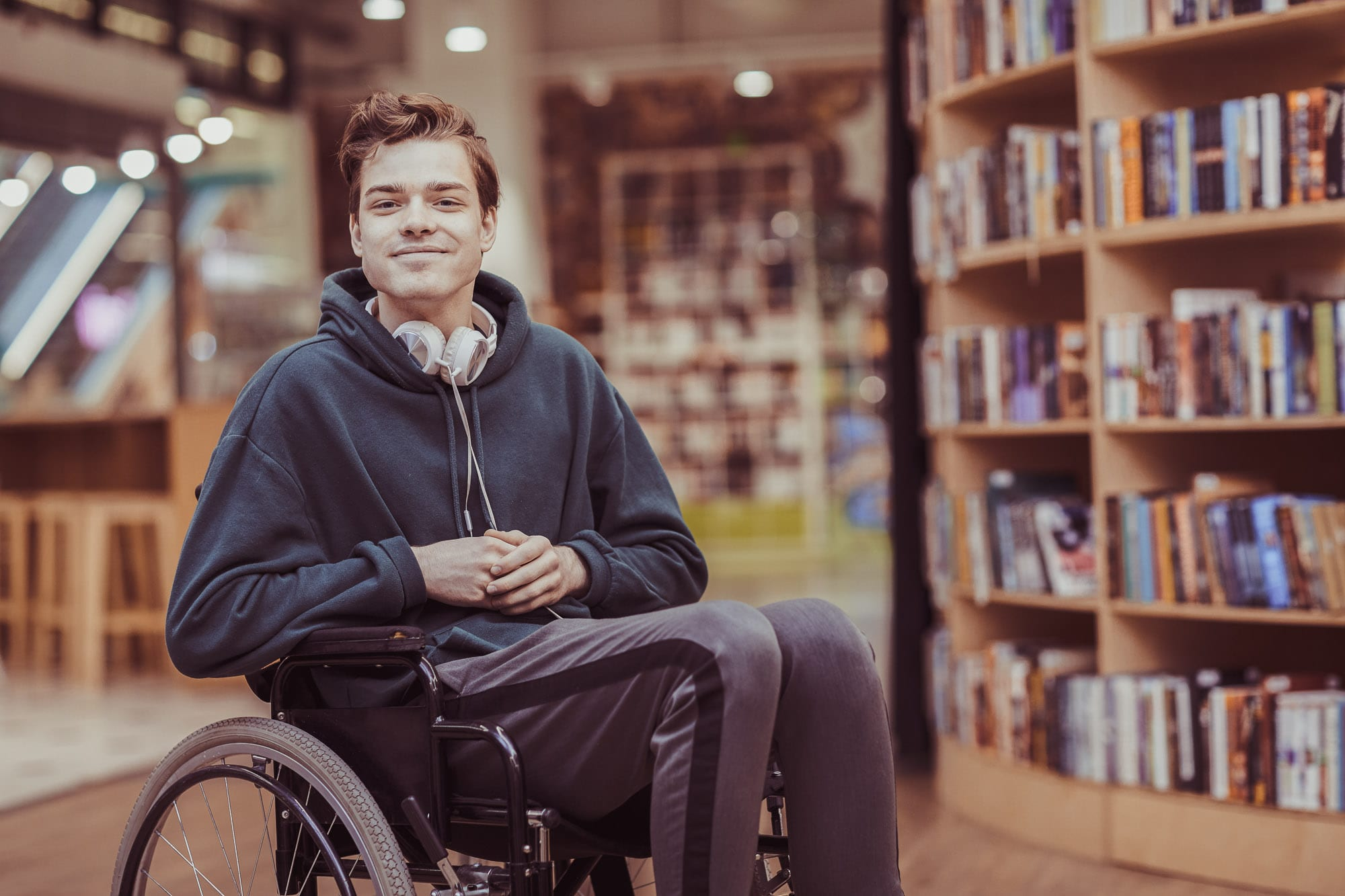 University student in a wheelchair in a library