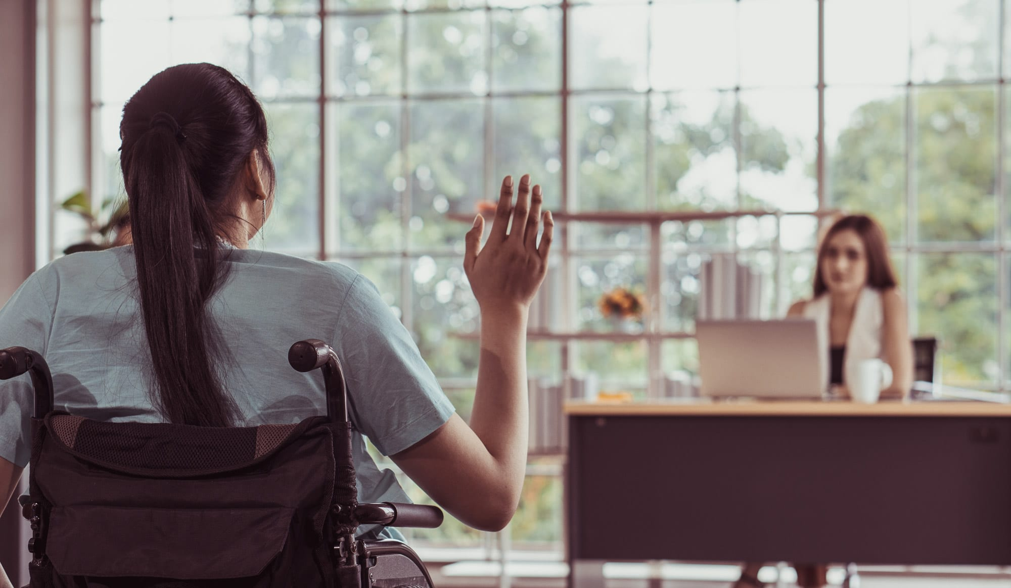 Woman in a wheelchair waving to an interviewer sat at a desk