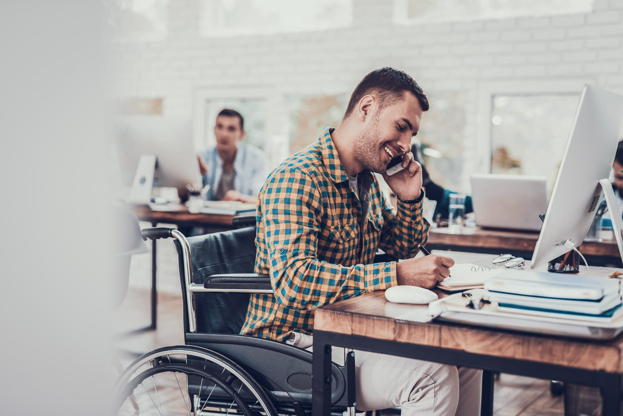 Man in a wheelchair on a phone in the office