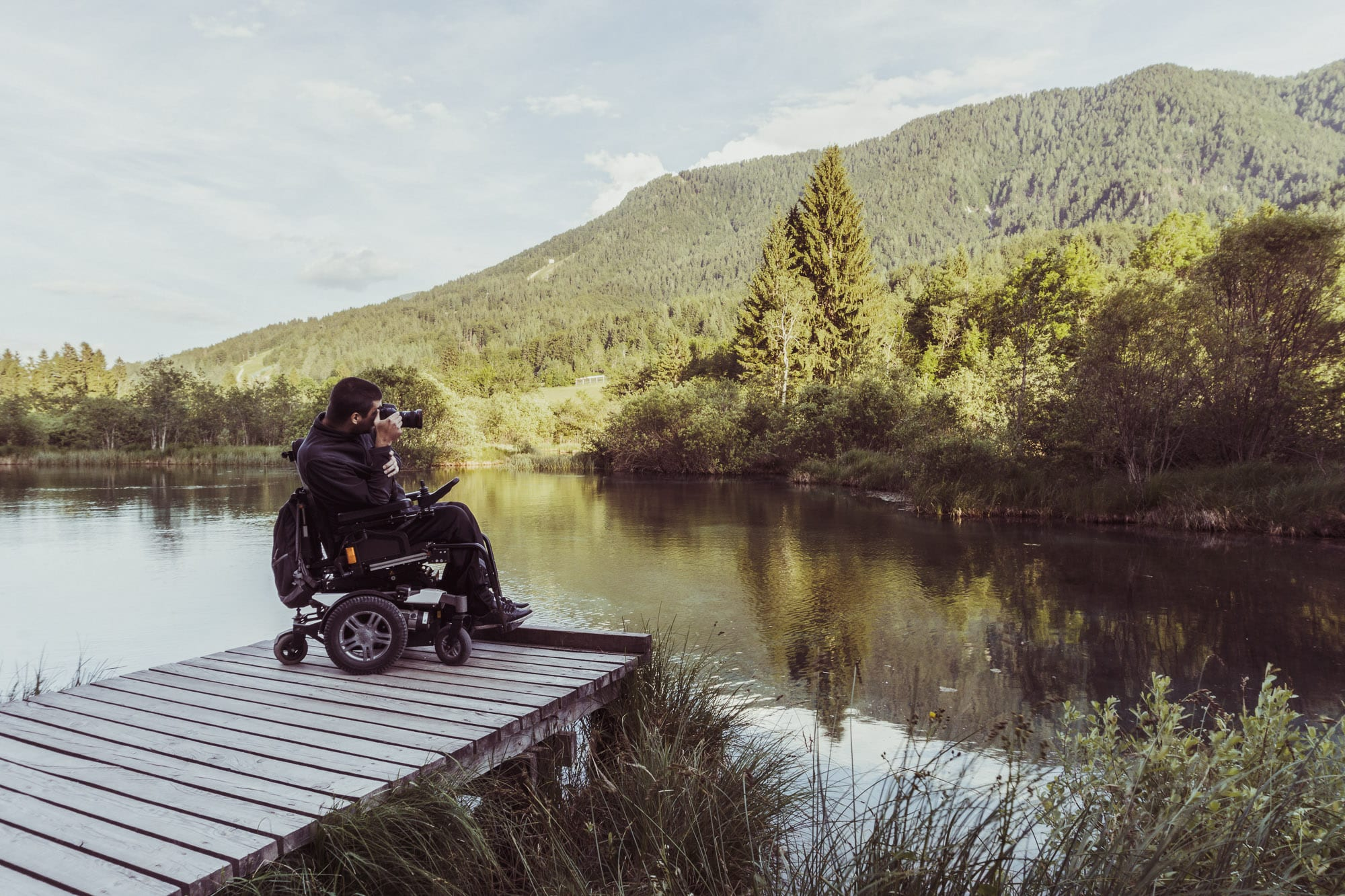Photographer in a wheelchair taking a photograph of mountains